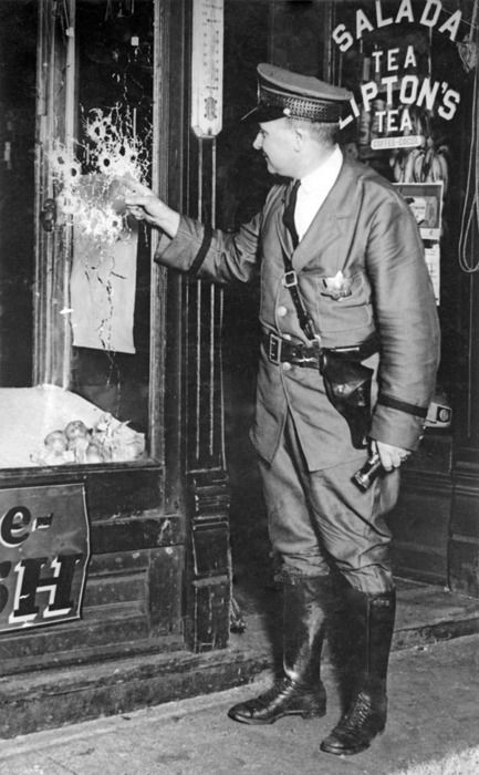 Chicago Police Officer Pat Barret examines 13 bullet holes in a glass window at the scene of an attempted murder, c. 1928
