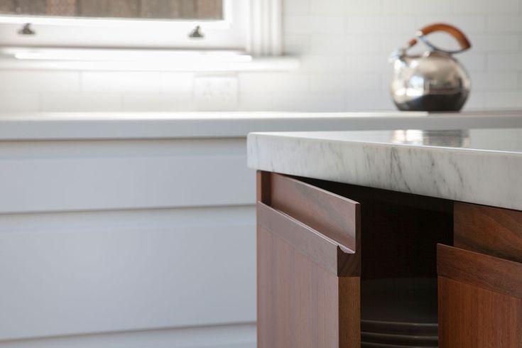 Detail of Carrara stone benchtop and finger groove in kitchen island cupboards. Island bench with grey ironbark veneer finish | Glenderg Grove by Mihaly Slocombe (2015) | Malvern, Victoria, Australia | photo: Tatjana Plitt