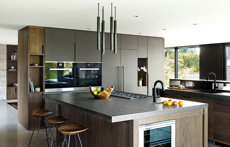 In this modern kitchen, dark wood has been paired with grey cabinets for a contemporary appearance. #GreyKitchen #Wood #KitchenDesign #ModernKitchen