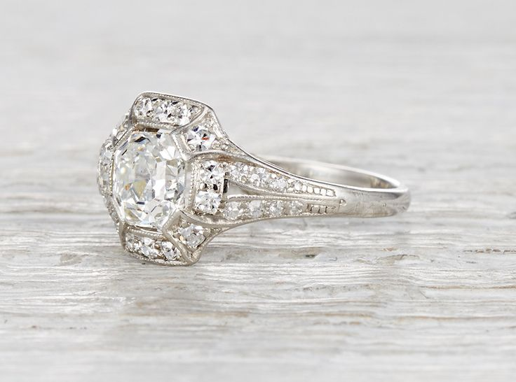 Vintage Art Deco platinum engagement ring centered with an EGL certified one carat asscher cut diamond with F-G color and VS2 clarity. Accented by single cut diamonds weighing .21 carats total. Circa 1920