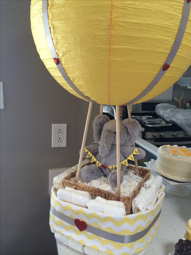 Instead of diaper cake, make a hot air ballon basket! We did a yellow and grey themed. The basket is wrapped with a chevron print blanket.