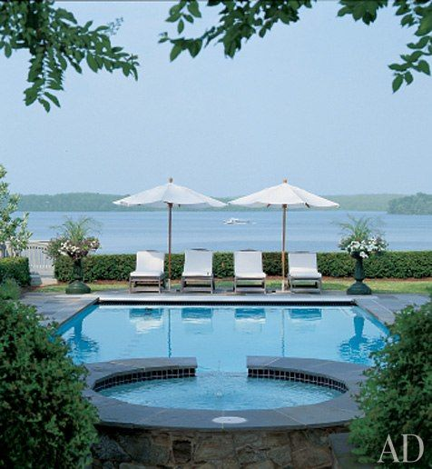 beautiful pool on the water, simple white furnishings neatly arranged balance the view from the house