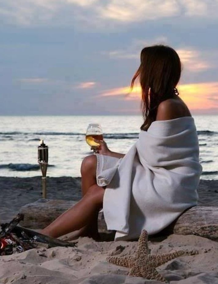 ".Lady wrapped in a blanket on the beach at dusk sipping on a glass of wine. Can you say ""how to relax and unwind"" ?"