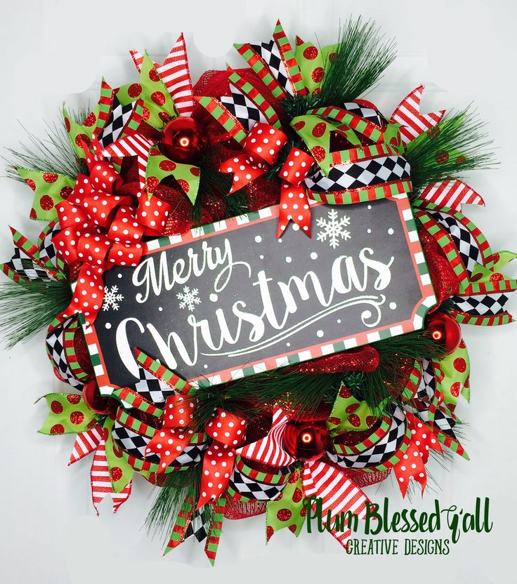 "Let the celebration begin at your front door with this ""Merry Christmas"" Deco Mesh Holiday Wreath!  This cheerful Christmas wreath is full of beautiful ribbons, ornaments and pine needles which accent the festive ""Merry Christmas"" wooden sign with layers and texture throughout the entire wreath."