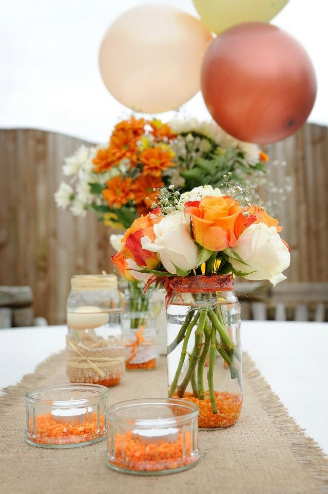 Our garden reception tables ... home made jam jar flower vases, hessian table runners, balloons (of course!)    candles.  Colour theme: orange and ivory  #wedding autumn  Photography: www.tinaallinghamphotography.co.uk