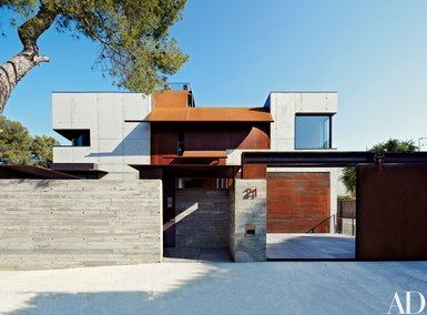 Tom Kundig of Olson Kundig Architects designed this industrial-style house/studio in Sitges, Spain. Walls of board-formed concrete and a roof of rusted Cor-Ten steel distinguish the two-story structure | archdigest.com