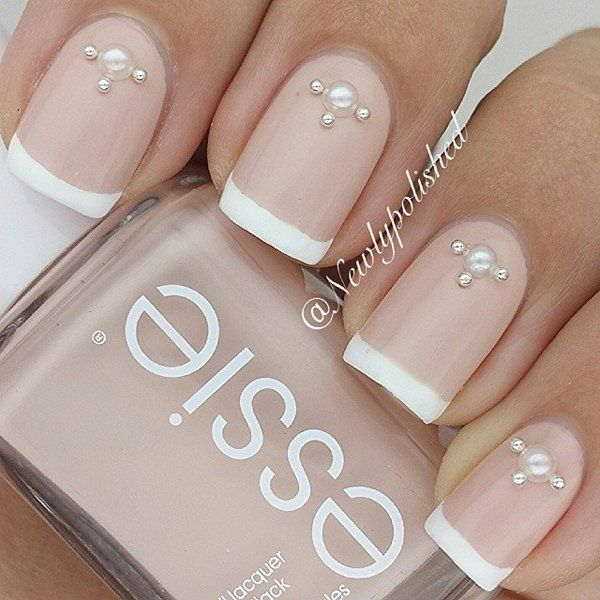 Nude and white nail polish combination. This nail art design uses nude nail polish with white French tips. Additional pearl and gold beads are also added on top for effect.