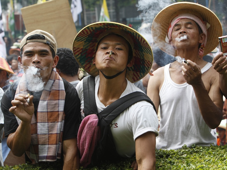 Tobacco farmers smoke cigarettes during a protest against a bill on stricter tobacco control in Jakarta, Indonesia, on July 3, 2012. Thousands of farmers staged the protest claiming that the bill that would ban cigarette advertising, prohibit smoking in public, and adding graphic images to packaging would lead to massive losses of job that would affect thousands of tobacco farmers and their families in Indonesia, the world's third-largest tobacco consumer. (AP Photo/Tatan Syuflana)