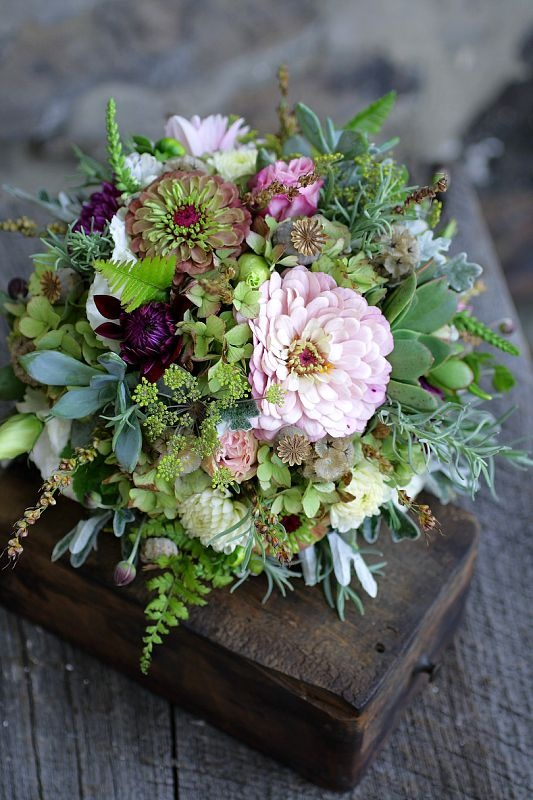 Pink zinnias with a touch of white and deep purple dahlias, succulents, and lots of greenery. Lovely bouquet.