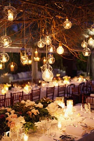 Natural branches with hanging light bulbs and votive candles