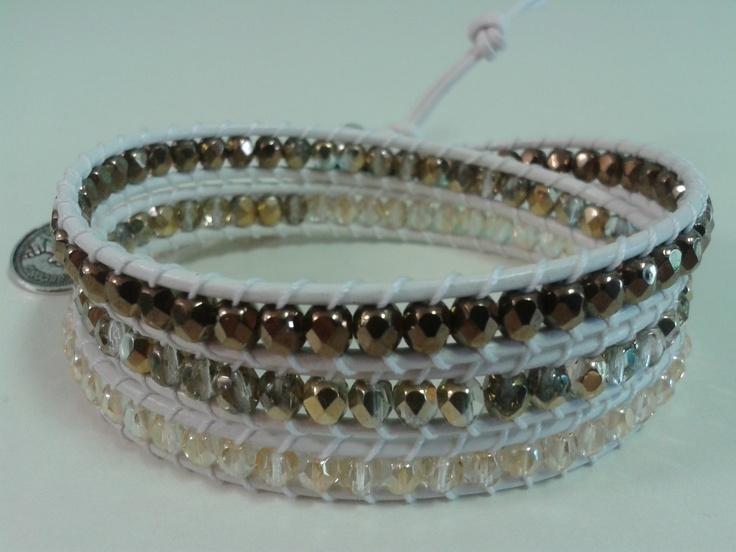 Tre giri in mezzi cristalli in vari toni d'oro, cuoio bianco e medaglia color argento.