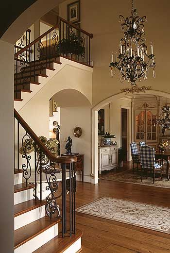 Love this look!  Chandelier, beautiful staircase w/ wrought iron, stained wood treads, built-ins in the dining room, hard wood floors w/ lovely rugs...traditional ... Love the whole look!