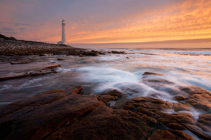 Slangkop Lighthouse, Kommetjie  The Slangkop Lighthouse awakes as night arrives in a dramatic display of sunset colors