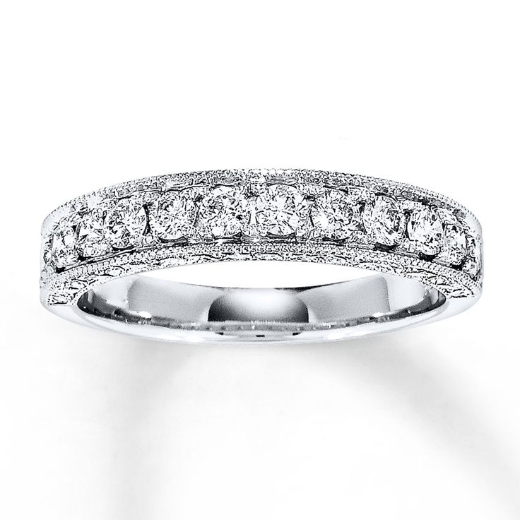 A row of round diamonds lends brilliance to this anniversary band for her, with a total diamond weight of 5/8 carat. This fine jewelry band is styled in 14K white gold, with milgrain finish and leaf designs on the sides to complete the look. Diamond Total Carat Weight may range from .58 - .68 carats.