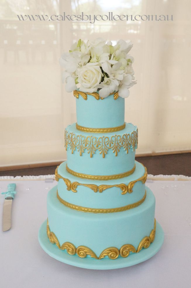 4 Tier teal & edible gold detail with fresh floral topper.