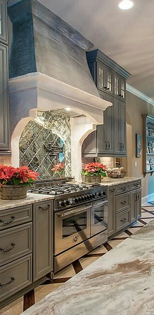luxury kitchen with antiqued grey cabinets, stainless steel, and mirrored tile