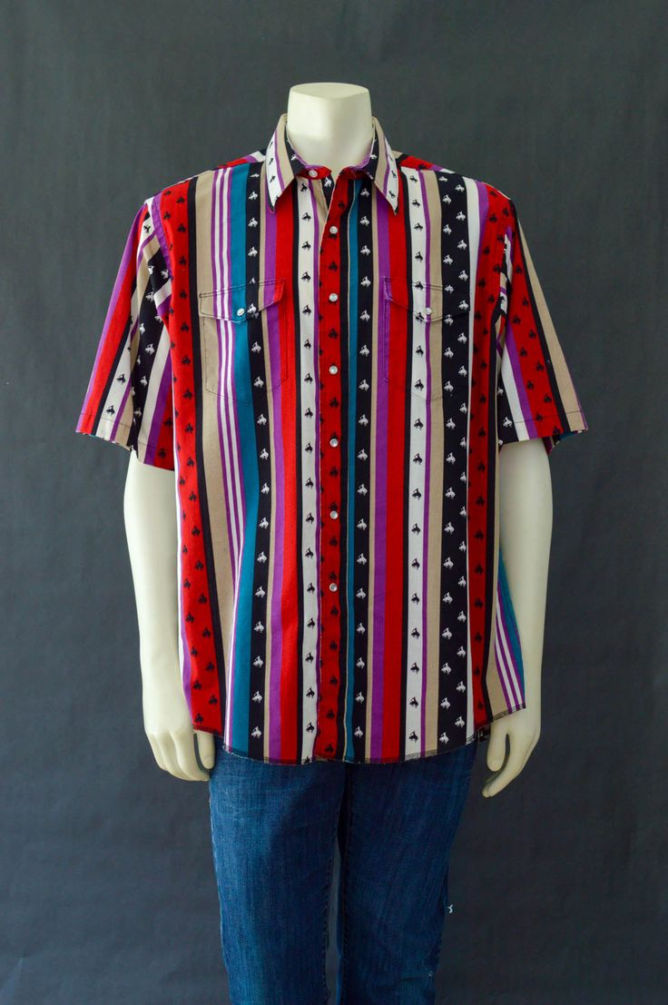 Bring that wild, wild west lifestyle to your wardrobe with this western print shirt! Array of bold earthy colors from black, red, tan, cream, white, indigo and purple.  Label *Wrangler *Cowboy Cut, Regular Fit *Western Shirt *X-Long Tails  Details *Wranglers Cowboy shirt is fresh and crisp *Collar is stiff and perfect for popping *Pearly white snap buttons for flair *Multi color and loud, we like it! *Southwestern party shirt with black and white cowboys riding horses, rodeo style. *Two…