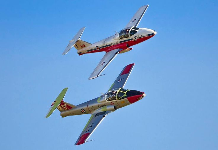 A CT-114 Tutor jet fighter displaying the Snowbirds distinctive paint scheme (top) and a Tutor with older markings perform a fly-past during the Tutor 50th anniversary celebration at 15 Wing Moose Jaw, Saskatchewan on October 3 – 4, 2014