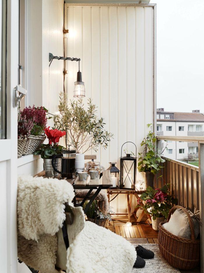 decoracion de terrazas, balcón con suelo de madera, mesa t sillas, cojines y cubierta de piel, linternas y flores