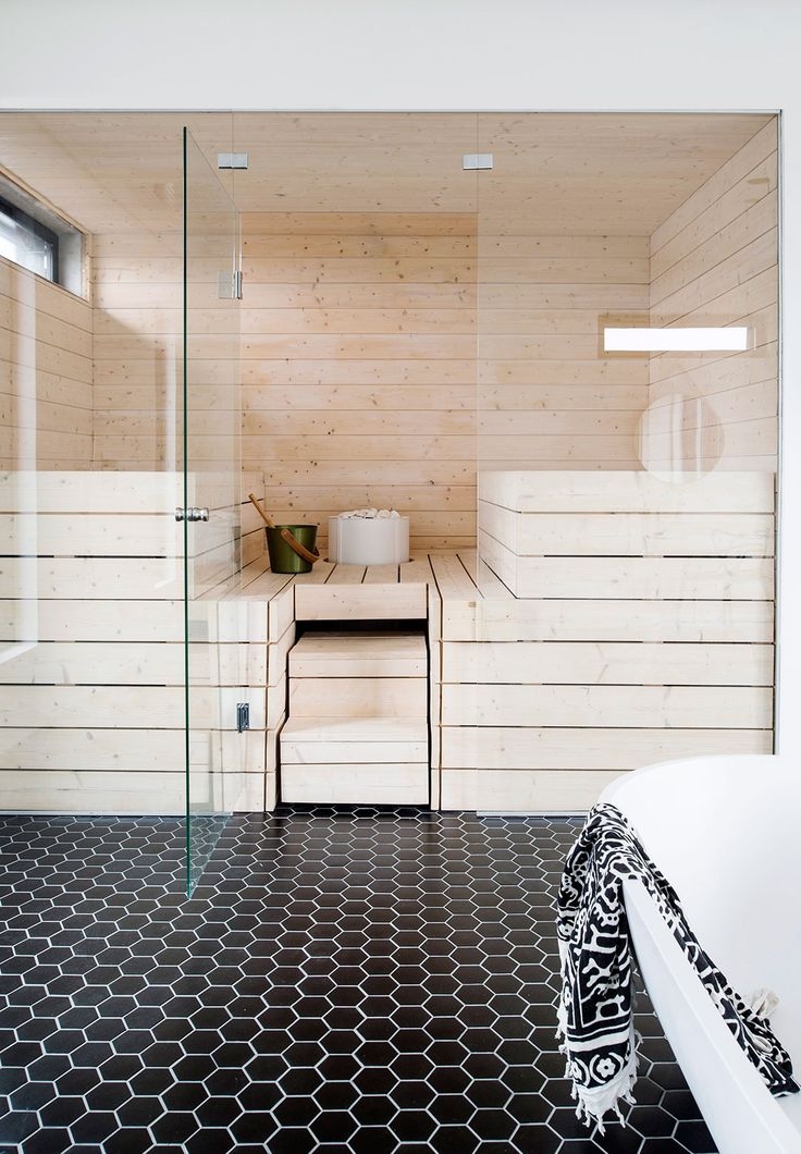 Kiuas on upotettu lehtikuusesta tehtyihin lauteisiin. Saunan ja kylpytilan välinen seinä on kokonaan lasinen ja helpottaa pienten kylpijöiden vahtimista saunan lauteilta.