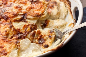 Ruth Chris Scalloped Potatoes ~ 5 medium russets 1 cup heavy cream 1/2 cup milk 1-1/2 Tbsp flour 1 clove garlic 1/4 tsp salt 1/8 tsp pepper 1 Tbsp butter softened 1 1/2 cups white cheddar cheese 1 tsp parsley Preheat oven to 400. Cut potatoes in 1/4 inch slices. Beat together cream, milk, flour,garlic, salt, & pepper. Coat baking dish with butter & layer half of potatoes, cream & cheese, repeat. Cover & bake for 20 minutes. Uncover & bake 40 minutes. Remove & sprinkle parsley on top
