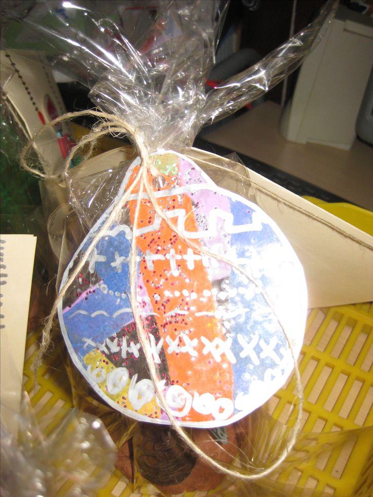 Bola decorativa a l'embolcall del regal: tires de paper de seda plastificades. retallar en forma de bola i fer grafismes amb retolador permanent (blanc, daurat o plata)