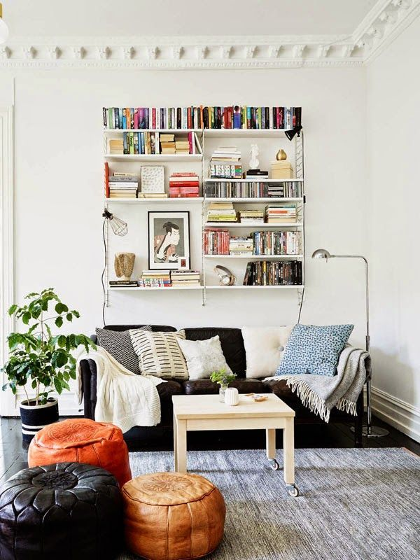 textural living room with open shelving above sofa and leather poufs