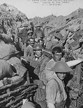 ".Repairing front line trench after bomb explosion fifty yards from enemy trenches. D. W. Griffith in civilian clothing. During filming of the motion picture ""Hearts of the World"" in France (1917)"