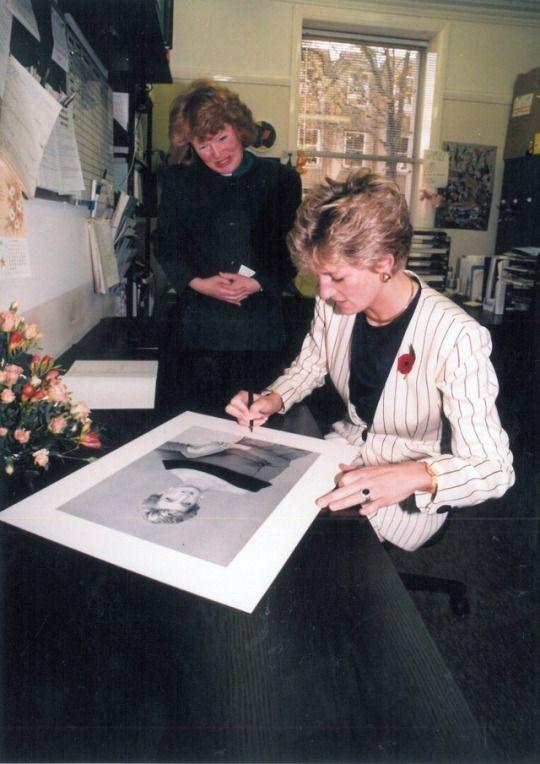 Princess Diana, circa November 1991, signing his a photograph of herself. Could be Kensington Palace. Princess Diana may have worn this jacket a lot. She was photographed in this jacket in 1989, in a chauffeur driven car (longer length hair).