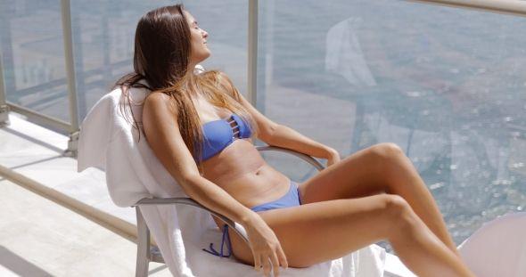 Girl Sunbathing on Hotel Balcony by Daniel_Dash Girl in bikini lying on chair and sunbathing in tropical sunlight while relaxing on balcony of luxurious resort hotel on background of ocean.