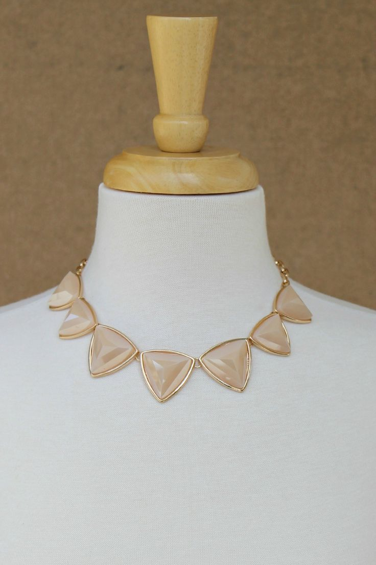 Dramatic meets classic and conservative in our chunky nude necklace, featuring faceted triangles set in bright gold. This one complements all skin tones and coordinates perfectly with those hard-to-match champagne tones.