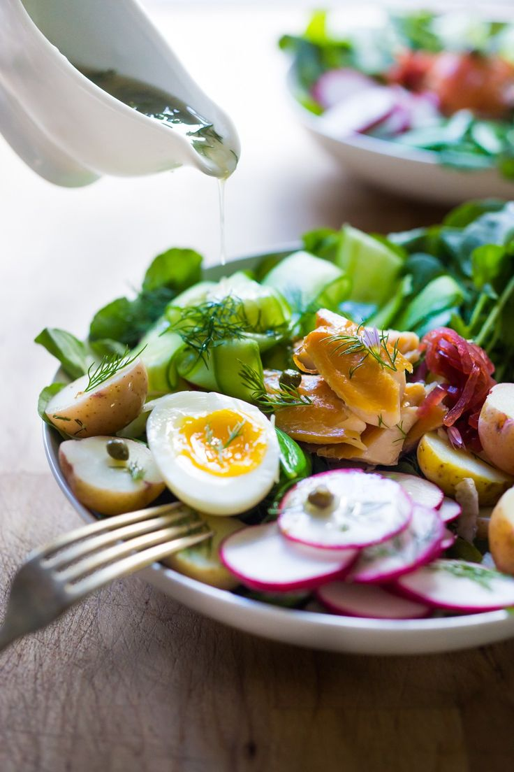 A Scandinavian twist on the classic nicoise salad - Nordic Nicoise Salad is made with smoked fish ( salmon, trout, sardines) or pickled herring, on a bed of watercress, with radish, cucumber ribbons, baby potatoes, capers, dill, chive blossoms and horseradish-spiked nicoise dressing. Fresh and tasty! | www.feastingathome.com