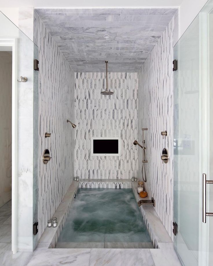 A walk-in shower and bathtub with a built-in television is one way to relax after a long day.  Designed by @joannabgoodman and @creebals @fixturesandfinishes #bathroomdesign #interiordesign #tileshower #bathroomremodel