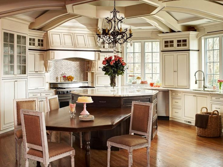 This gorgeous French country kitchen makes the most of an unusual space with stunning ceiling details and an elegant chandelier. A wooden breakfast table attaches to the octagonal island to make the most of the space.