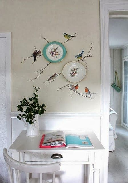 pratos na parede com pássaros pintados ao redor