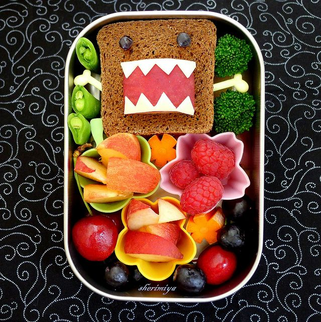 What a fun bento lunches for kids idea featuring a cream cheese sandwich on rye cocktail bread. The eyes are made of bits of grapes, the  mouth a red plum, and the  teeth are cut from mozzarella. I also love the fruit and the veggies that round out this snack/bento lunch. For more creative ideas for kids lunches LIKE US on Facebook @ https://www.facebook.com/SchoolLunchIdeas