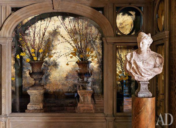 Фрагмент столовой. В отличие от гостиной, тут нет сада за окнами. Это помещение используется в основном в вечернее время для семейных обедов. Архитекторы решили восстановить справедливость и превратили окно в нишу с живописным полотном тромплей — холст пропускает свет в комнату, и создается иллюзия тенистого парка. Такая атмосфера характерна для особняков XVII–XVIII веков, ее поддерживает садовая скульптура той же эпохи (отреставрированная, но сохранившая следы мха).