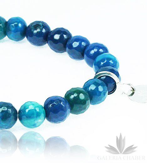 Bransoletka wykonana z kamieni naturalnych, fasetowanych, o barwie chabrowej, niebieskiej, zielonkawej. Ozdobiona frędzelkiem bawełnianym oraz blaszką firmową, wykonaną ze srebra próby 925. Kamienie nawleczone na gumkę dopasowują się do obwodu nadgarstka. Bransoletka fantastycznie uzupełni strój jako ozdoba nie tylko sama, ale także w towarzystwie innych bransoletek w podobnych odcieniach. Polecamy także bransoletki wykonane z kamieni naturalnych w innych odcieniach, dostępne na Galerii.