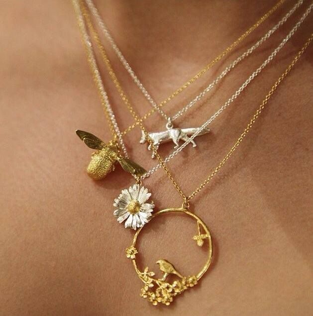Beautiful stack of necklaces including our iconic Bumblebee, Big Daisy, Prowling Fox and Bird in Loop Necklaces