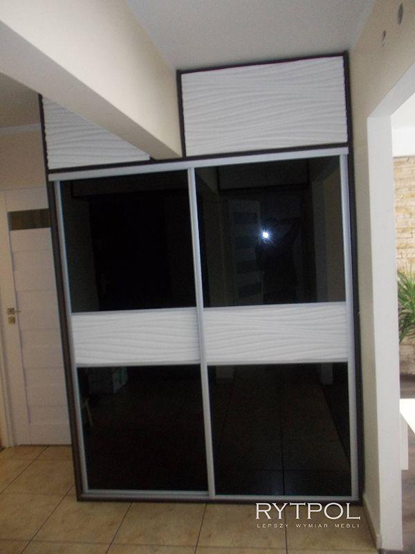 Zabudowa przedpokoju. Szafa wnękowwa wykonana z płyty. Drzwi przesuwne wypełnione czarnym lacobelem oraz wstawką z tłoczonego mdfu polakierowanego na biały kolor. W szafie została zabudowana pralka.