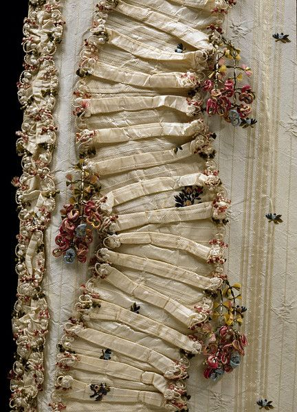 Two types of fly fringe (braid) adorn this sack-back gown of about 1770, one as a trim, the other as a tassel.  The gown is made of ivory silk figured with stripes and floral stripes and brocaded with floral sprays in yellow, blue, green and shades of pink. The degree to which the colours of the fringes complement each other and the gown suggests that they may have been made to match.    V
