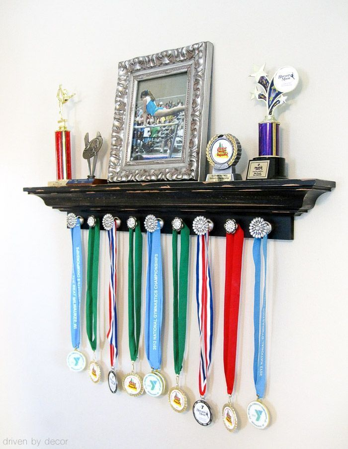 Such a cute way to display your kid's trophies and medals - shelving for the trophies and knobs for medals! #soccerBoysandGirls