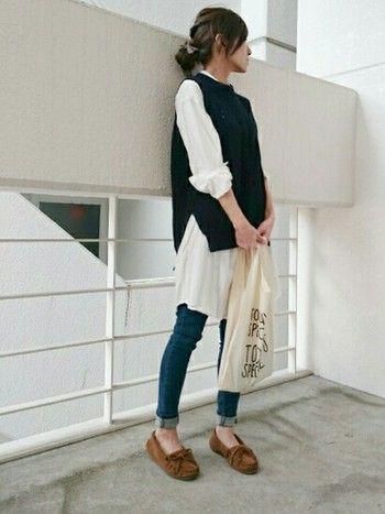 シンプルなホワイトのシャツワンピースには、細身のデニムとニットベストを合わせてクールなイメージに。ベストはサイドにスリットの入った広がりのあるデザインだから、きれいにシャツワンピも広がります。