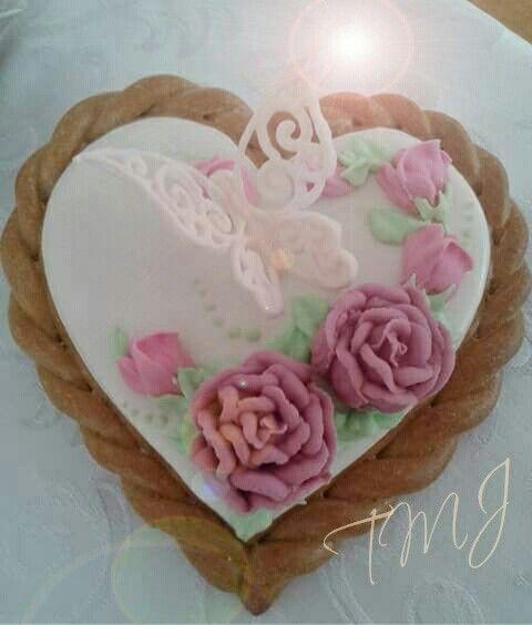 Lila rózsákkal és glazúr csipke pillangóval díszített mézeskalács szív./ Gingerbread heart cookie decorated with purple roses and lace frosting butterfly.