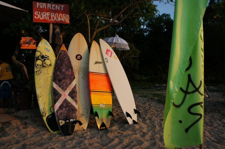 Surfing boards on Jimbaran Beach next to The Open House Bali ready for riding the waves.