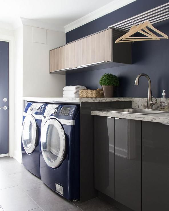Contemporary laundry room features gray lacquered cabinets by Ikea topped with gray and white quartz countertops which resemble marble fitted with a stainless steel sink and satin nickel faucet tucked under a 6 drying rods.