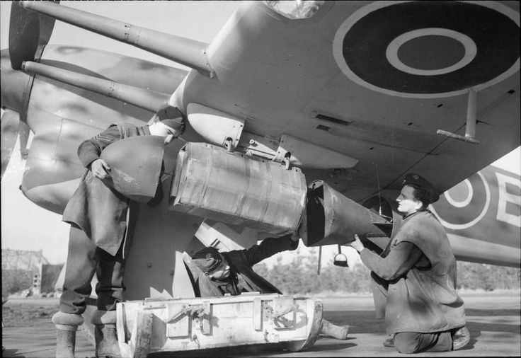Armourers attach the nose and tail units onto a cluster projectile containing 26 x 20-lb anti-personnel bombs, fitted under the wing of a Hawker Typhoon Mark IB of No. 439 Squadron RCAF at B78/Eindhoven, Holland.