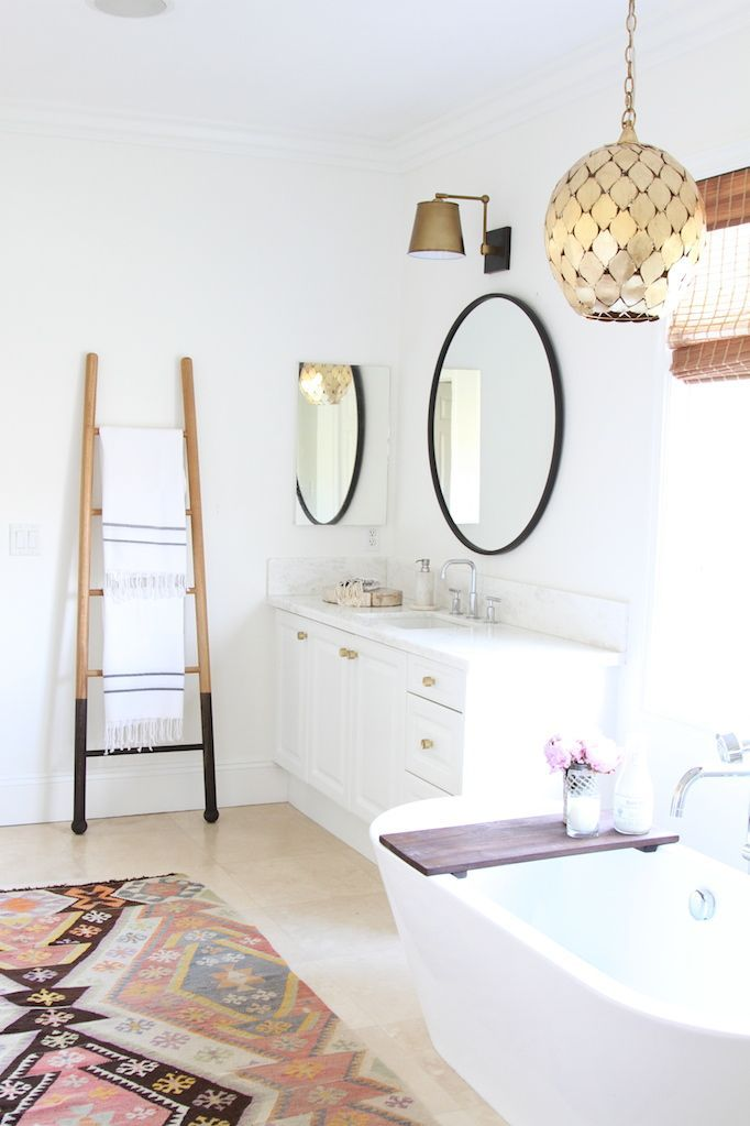 BECKI OWENS - Las Palmas Project: Modern Bohemian Master Retreat. White bathroom with Moroccan accents, brass lighting and hardware, round mirrors, marble counters, free-standing tub, vintage kilim rug, and Turkish towels.