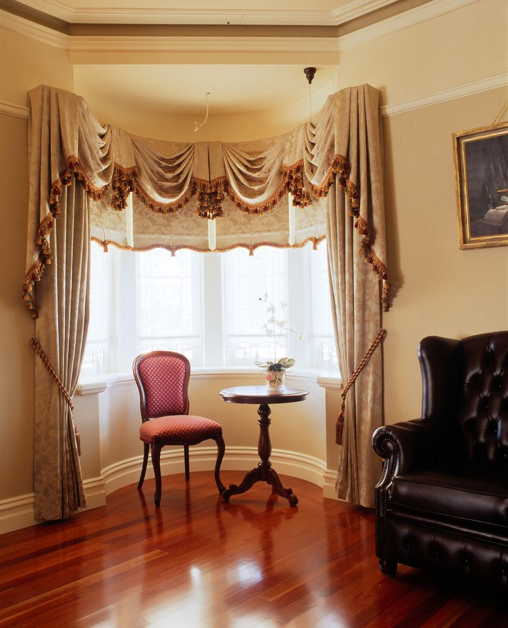 Bay window with swags and tails and matching drapes and blinds.