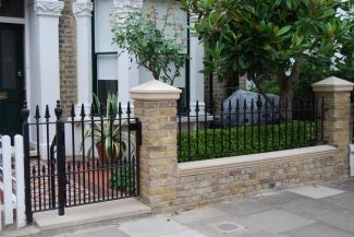 Exposed brick wall with cap stones and iron railings